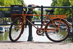 Orange bike on an Amsterdam Canal. Holland Royalty Free Stock Images
