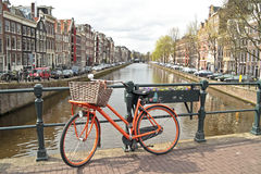 Orange bike in Amsterdam city in the Netherlands. Orange bike on the bridge in Amsterdam city in the Netherlands Stock Photos