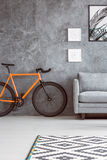 Orange bike next to sofa Stock Photos