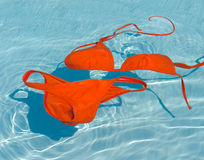 Orange bikini in clean water. Swim suit floating in a swimming pool Royalty Free Stock Photo