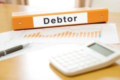 Orange  binder debtor on desk in the office with calculator Royalty Free Stock Image