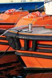 Orange and black boats moored in the port - Italy stock images