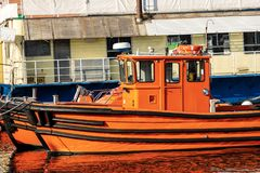 Orange and black boats moored in a port - Italy stock photography