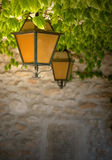 Orange and Black Lanterns. Two black wrought-iron lanterns with orange glass, hanging from a vine-covered ceiling against a stone wall. Taken in an ancient stock photos