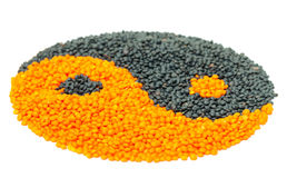 Orange and Black Lentil forming a yin yang symbol Royalty Free Stock Photography