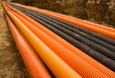Orange and black plastic pipes Stock Image