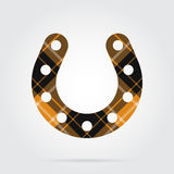 Orange, black tartan icon - horseshoe with holes. Orange, black isolated tartan icon with white stripes - horseshoe with holes and shadow in front of a gray Royalty Free Stock Image