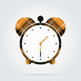 Orange, black tartan isolated icon - alarm clock. Orange, black isolated tartan icon with white stripes - alarm clock and shadow in front of a gray background Royalty Free Stock Photos
