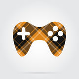 Orange, black tartan isolated icon - gamepad. Orange, black isolated tartan icon with white stripes - gamepad and shadow in front of a gray background Royalty Free Stock Photos