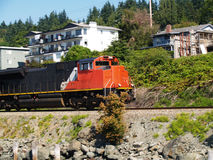 Orange and Black Train Engine Going Down Tracks Stock Images