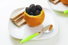 Orange and blackberry. This dessert was made ​​by placing an orange and digging into it the delicious blackberries Stock Photo