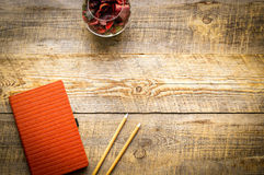 Orange Blank notebook with flower on vintage wooden table Stock Photography