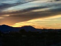 Orange blaue Sonnenaufgang-Sonnenuntergang-Wolken über Bergen Stockbilder