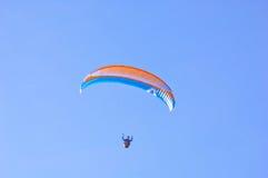 Orange blauer heller Gleitschirm im blauen Himmel Stockbilder