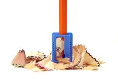 Orange Bleistift in einem blauen Bleistiftspitzer Stockfotos