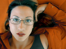 Orange Bliss. Woman lays surrpunded by orange Royalty Free Stock Photography