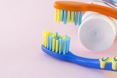 Close-up of baby toothbrushes and toothpaste on color background. Orange and blue baby toothbrushes and toothpaste on pink background Royalty Free Stock Photo