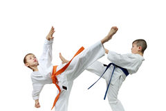 With orange and blue belts  the sportsmen are beating kicks Stock Photo