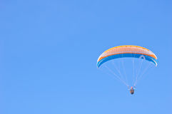 Orange blue bright Paraglider in blue sky. Orange blue Paraglider in blue sky. Sport and hobby Royalty Free Stock Photo