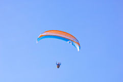 Orange blue bright Paraglider in blue sky. Paraglider in blue sky. Sport and hobby Stock Images