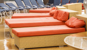 Orange and Blue Chaise Lounges on a Wet Deck. Orange and blue chaise lounges on a ship's deck in the rain stock photos