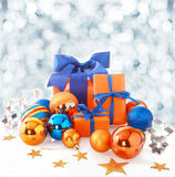 Orange and blue Christmas background. With color themed gifts and baubles arranged with stars and cookie cutters against a backdrop of falling winter snowflakes Stock Photo