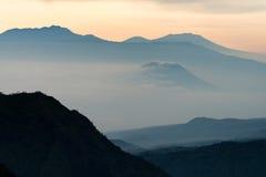 Orange blue light foggy silhouette mountain Royalty Free Stock Images