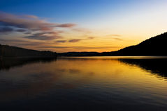 Orange blue sunrise at swedish lake with mountains Stock Photos