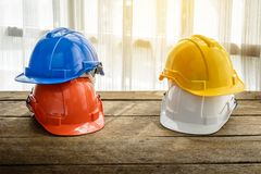 Orange, blue, yellow, white hard safety helmet construction hat Royalty Free Stock Image