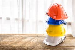Orange, blue, yellow, white hard safety helmet construction hat Stock Images