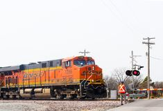 Orange BNSF railroad freight train engine stopped at rural intersection with flagman out inspecting and gate down near Claremore O. An Orange BNSF railroad Royalty Free Stock Images