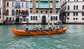 Orange Boat. Venice,Italy- February 19, 2012: A red boat with a group of funny disguised people sailing on the Grand Canal in a boats parade during the Carnival Stock Image