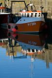 Orange boat and blue sky reflection. Upright image of small orange fishing boat against the harbour wall in Padstow, Cornwall with the blue sky reflected in the royalty free stock images