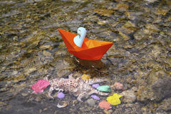 Orange  boat floating in the water at the bottom of colorful seashells Royalty Free Stock Photo
