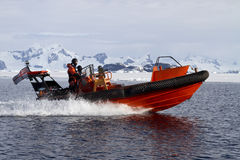 Orange boat sailing at high speed in Antarctic waters against mo Stock Image