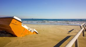 Orange boat in the sands of the winter beach waiting for the summer months to arrive, Cyprus. Orange boat in the sands of the winter beach waiting for the summer royalty free stock image