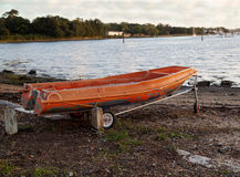 Orange boat tender. Colorful old orange boat tender on a trolley by a public slipway on a cloudy day Stock Photography