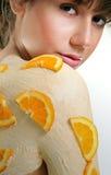 Orange Body Mask. Beautiful Girl with Orange Body mask and Orange slices on her shoulder isolated on white background Stock Photography