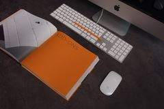 Orange Book in Distance With Silver Imac Royalty Free Stock Images