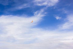 Orange boomerang flying in the sky Royalty Free Stock Photos