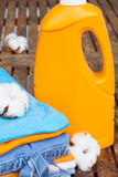 Orange bottle of detergent and cotton clothes Royalty Free Stock Photo