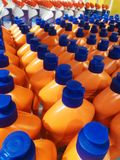 Orange bottles with detergent in the shop. A lot of orange bottles with detergent in the store Stock Images