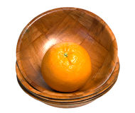 Orange In A Bowl. A fresh orange sitting in a wooden bowl at the top of a stack, isolated against a white background Stock Images