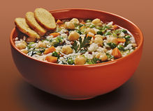Orange bowl of rice soup with lentils and peas chickpeas Royalty Free Stock Photo