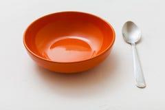 Orange bowl and spoon on white plaster Stock Photos