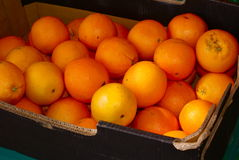 Orange box. Box of juicy oranges on an open air market stall. Fresh fruit contain vitamin C and can be eaten or used for marmalade Stock Photos