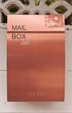 Orange braune Metalmailbox auf Wand Stockbilder