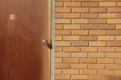 Orange brick wall. Rusty door with doorknob next to orange brick wall Royalty Free Stock Photo