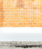 Orange brick wall with white cement painted wall and pavement an Stock Photo