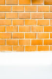 Orange brick wall with white cement painted wall and pavement an Stock Photos